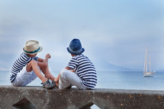 Two similar brother sitting on waterfront, Stock Photos
