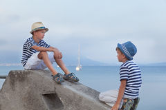 Two similar brother sitting on waterfront,. Talking , watching ship Stock Photos