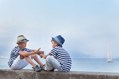 Two similar brother sitting on waterfront,. Talking , watching ship Royalty Free Stock Photos