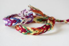 Two simple handmade homemade natural woven bracelets of friendship on white background, rainbow colors, checkered pattern. Simplicity, isolated Stock Photos