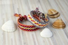 Two simple handmade homemade natural woven bracelets of friendship on white wooden table and sea shells Stock Photo