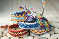 Two simple handmade homemade natural woven bracelets of friendship on white wooden table and stones. Two simple handmade homemade natural woven bracelets of Royalty Free Stock Photos