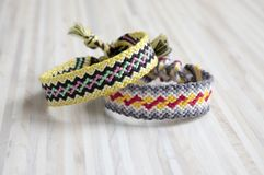 Two simple handmade homemade natural woven bracelets of friendship on white wooden table. Rainbow colors, checkered pattern Royalty Free Stock Images