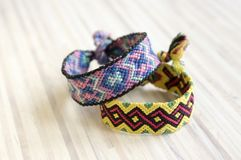 Two simple handmade homemade natural woven bracelets of friendship on wooden table Royalty Free Stock Photography