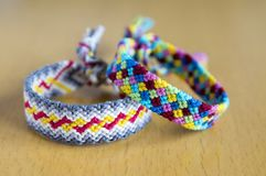 Two simple handmade homemade natural woven bracelets of friendship on wooden table. Two simplicity handmade homemade natural woven bracelets of friendship on Royalty Free Stock Photography