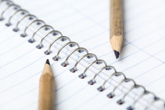 Two simple pencil. On the background of notebook Stock Photos