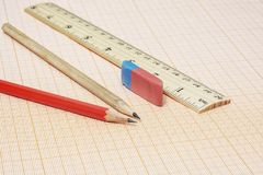 Two simple pencils, an eraser and a ruler on a millimeter paper. On the millimeter paper there are two simple pencils with an eraser and a ruler stock photo