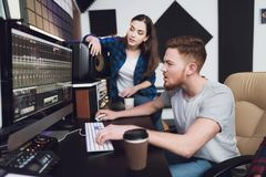 Two singers and sound engineers in the recording studio. They are engaged in mixing the songs of girls. They are in a modern recording studio stock photography