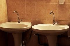 Two sinks with tap on background of tiles. Two sinks with a tap on the background of tiles royalty free stock photography