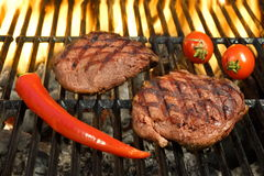 Two Sirloin Beef Steak On The Hot Flaming BBQ Grill. Two Sirloin Beef Steak, Tomato And Chili Pepper On The Hot Flaming BBQ Grill, Close Up, Top View Stock Image