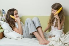 Two sister children in pajamas play in the morning in bed. Keep bananas as phones talking and laughing Stock Images