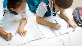 Two sister girl writes a book. The decision of lessons. girl lay down drawing the picture royalty free stock images