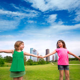 Two sister girls friends playing holding hand in urban skyline Stock Photo