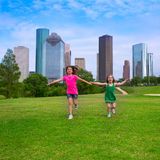 Two sister girls friends running holding hand in urban skyline Stock Image