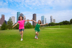 Two sister girls friends running holding hand in urban skyline Royalty Free Stock Images