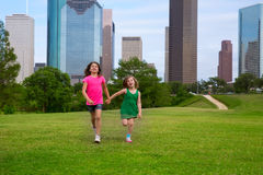 Two sister girls friends running holding hand in urban skyline Stock Photos