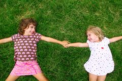 Two sister girls lying on meadow green grass Stock Photos