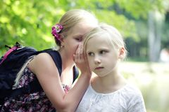 Two Sister Girls Whisper In Ear outdoors.  Surprise. Emotion of happiness.  stock images