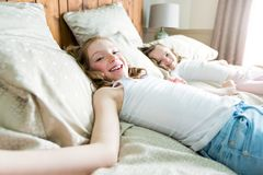 Two sister lay bed at home Royalty Free Stock Images