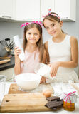 Two sister mixing ingredients for dough in big bowl on kitchen Stock Image