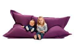 Two sister sitting on beanbag Royalty Free Stock Photo