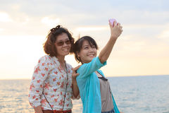 Two sister take a photo,selfie by smart phone beside sea beach w Royalty Free Stock Images
