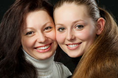Two sisters. A portrait of two young attractive girls.On black background Royalty Free Stock Image