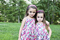 Two Sisters. Best Friends and sisters  looking as if they might be up to something.  They are beautiful little girls with sweet expressions.   They have brown Stock Image