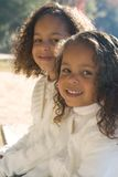 Two sisters. Two beautiful mixed race sisters enjoying the park Stock Image