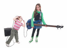 Two sisters. One with an electric blue bass and the younger biting the cable teasing her older sister Royalty Free Stock Photo
