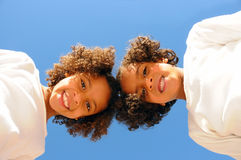 Two sisters. A cute, vertical view of two young sisters leaning over, looking straight down at the camera Royalty Free Stock Photo
