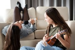 Two sisters alone in the house having fun and playing royalty free stock image