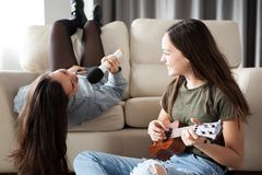 Two sisters alone in the house having fun and playing stock images