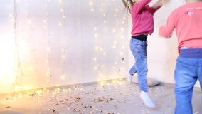 Two sisters from American family playing fun and throwing one on one holiday confetti. Two girls of American appearance play and have fun jumping in living room stock footage