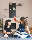 Two sisters amusing themselves with a bell at Christmas. Two sisters amusing themselves with a bell Royalty Free Stock Image