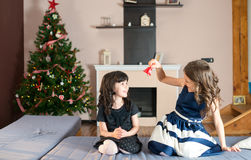 Two  sisters amusing themselves with a bell at Christmas Stock Photo