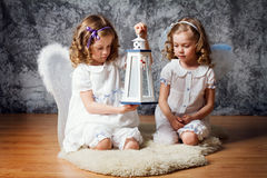 Two sisters with angel wings play with flashlight stock photography