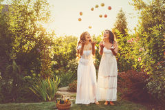 Two sisters apples and pears. Two cute sisters in long white dresses tossed up the harvest of apples and pears. Ripe fruits and vegetables. A bountiful harvest Royalty Free Stock Photo