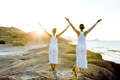 Two Sisters Are Doing Yoga Exercises At The Seashore Of Mediterr