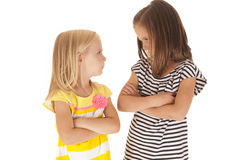 Two sisters with arms folded angry looking at each Stock Photography