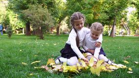 Two sisters in an autumn park. Are sitting on the lawn. They pull the fallen yellow and red sistya from the wicker basket stock video footage