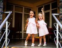 Two sisters baby girls in the same dresses, holding hands. Small sweet sisters, dressed the same dresses, holding hands, having fun, happy family Royalty Free Stock Photography
