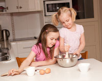 Two sisters bake muffins Stock Photos