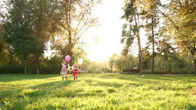 Two sisters with balloons. Family picnic. Two sisters are running with balloons. Family time. Concept of a happy family stock footage