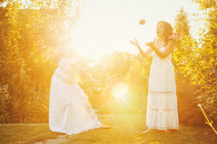 Two sisters and a basket of crop. Two cute sisters in long white dresses and a basket with harvest. She catches eggplant. Ripe fruits and vegetables. A bountiful Royalty Free Stock Photography