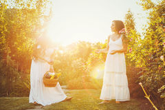 Two sisters and a basket of harvest. Two cute sisters in long white dresses and a basket with a crop. Girl shows her sister harvest. Ripe fruits and vegetables Stock Photos