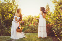 Two sisters and basket of harvest. Two cute sisters in long white dresses and a basket with harvest. Girl shows her sister harvest. Ripe fruits and vegetables Stock Images