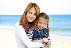 Two sisters at the beach in sunny autumn day Stock Image