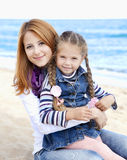 Two sisters at the beach in sunny autumn day Stock Photo