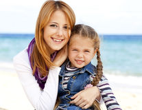 Two sisters at the beach in sunny autumn day Royalty Free Stock Photos